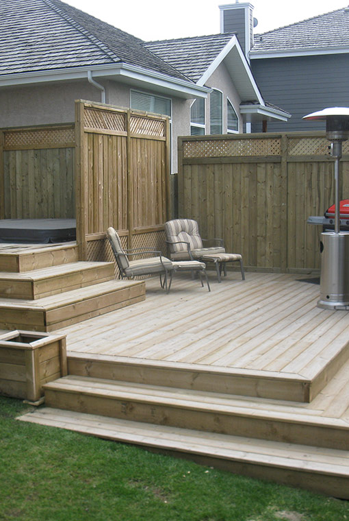 backyard Pressure treated lumber deck with fence and patio chairs