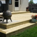 pressure treated wood deck with flower pots and fire place
